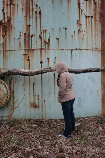 Full length of woman wearing hooded shirt against rusty water tank