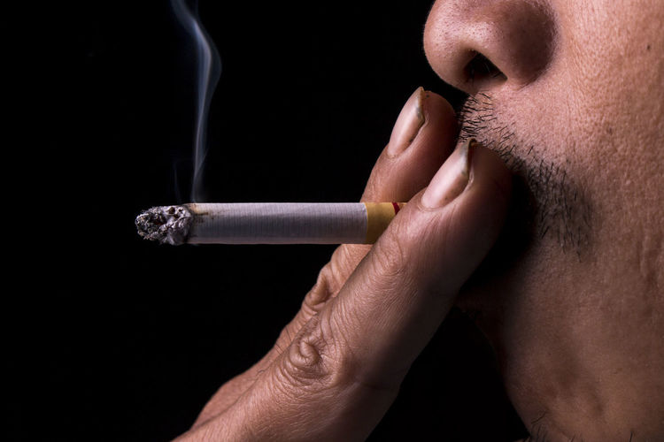 Cropped Image Of Man Smoking Cigarette Against Black Background