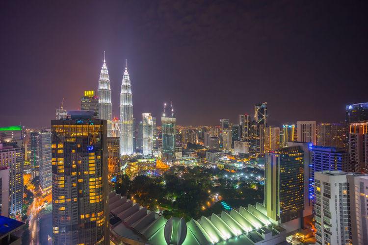 Illuminated petronas tower in city against sky