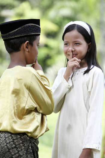 malay kids with traditional clothing. Finger over mouth. Psst Baju Melayu Hari Raya Aidilfitri Innocence Ramadan  Traditional Clothing Whispering Baju Kurung Boys Child Childhood Cute Different Cultures Elementary Age Friendship Girl Lifestyles Malay Malaysia Outdoors Park - Man Made Space Real People Secret Silence Togetherness Two People