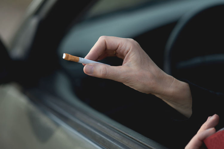 Cropped hand holding cigarette while sitting in car