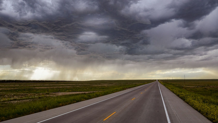 Empty country road against cloudy sky