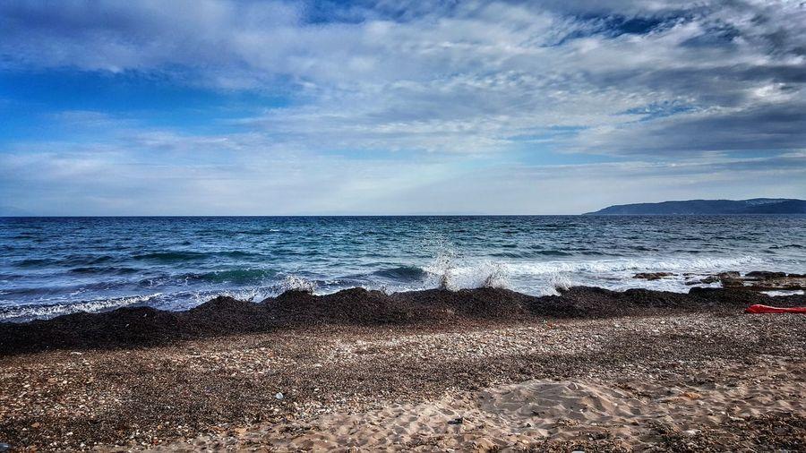 Waves in sea splashing at shore against sky