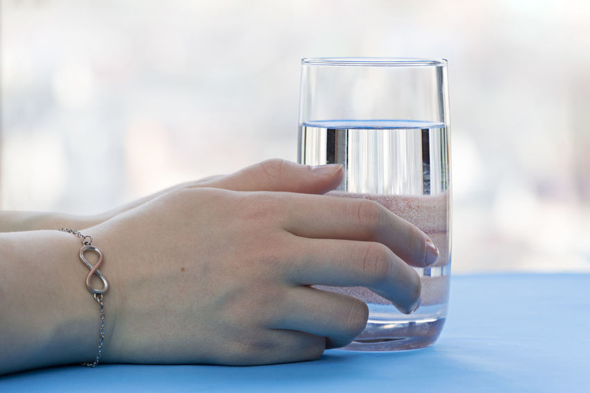 A glass of water in hands Water Glass Glass Of Water Hand Holding Water Clean Water Slimming Drink Diet Health Healthy Diet Healthy Drinks Healthy Life Healthy Food Artesian Artesian Water Water Source Water Resources Resource  Life Lifestyle Girl Woman Table