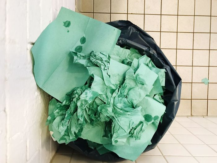 High angle view of papers in bin bag on floor