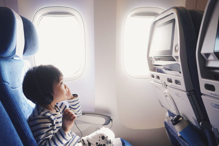 Side view of boy sitting in airplane