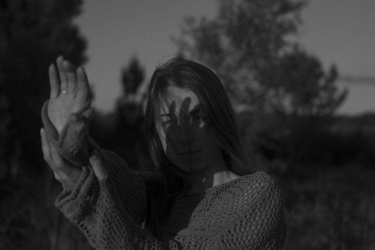 Portrait of woman shielding eyes