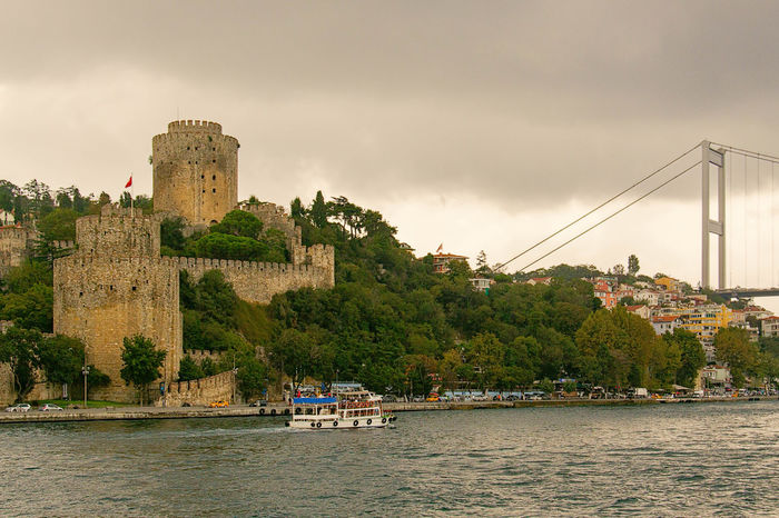 Rumeli Hisari Architecture Boat Built Structure Castle, Fortress, Protection, Fort, Security, Ancient, Dominating City Cloud Cloud - Sky Cloudy Day Fortress, Fort, Stronghold, Fortification, Keep, Citadel Mode Of Transport Nature Nautical Vessel Outdoors River Rumeli Hisarı Rumelihisari Scenics Sky Tranquil Scene Travel Destinations Tree Turkey, Istanbul, Europe, European, Asia, Asian, Bosphorous, Water, Black Sea, Sea, Water Waterfront