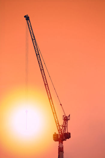Silhouette cranes against romantic sky at sunset