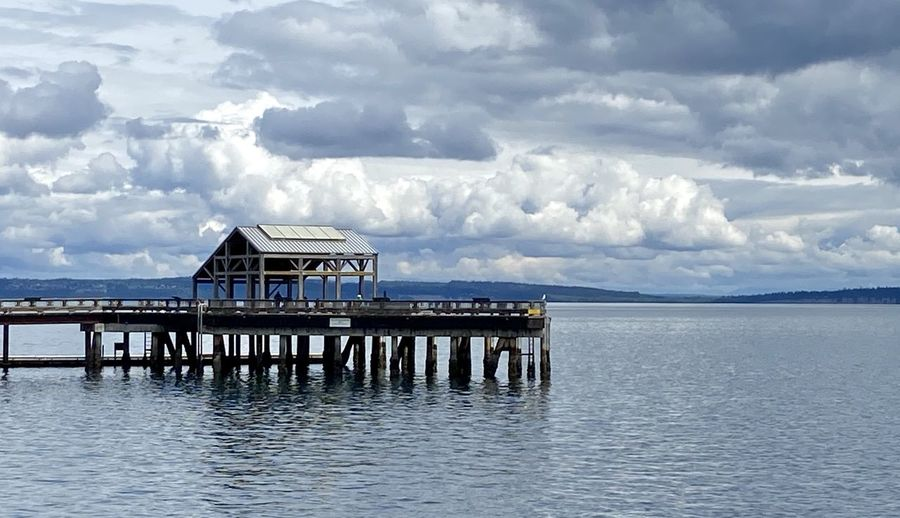 Stilt house on sea by building against sky