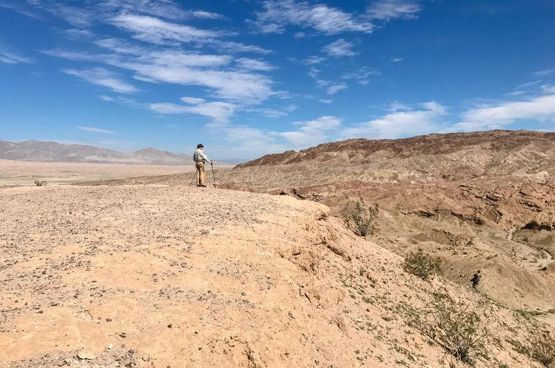 Side View Of Senior Man Standing On Sand At Desert Against Blue Sky