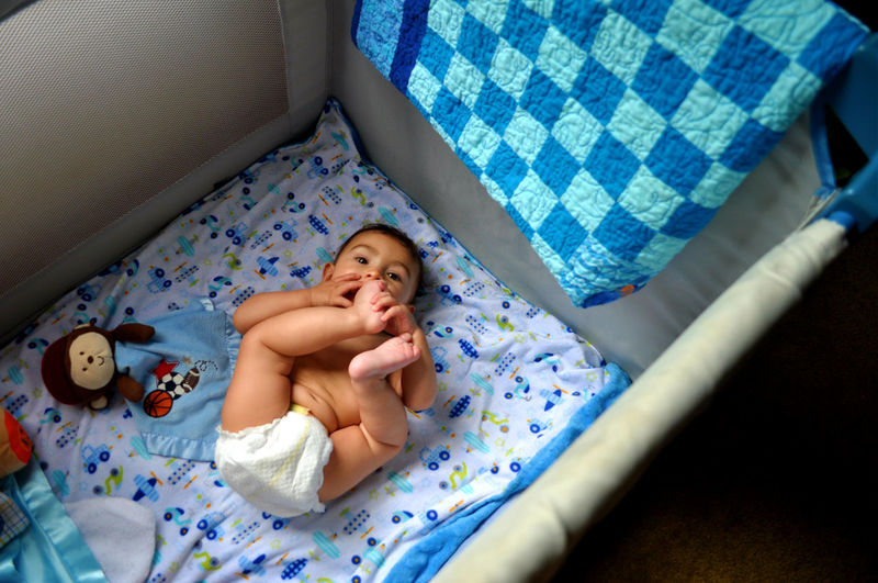 High angle view of cute baby boy lying in crib at home