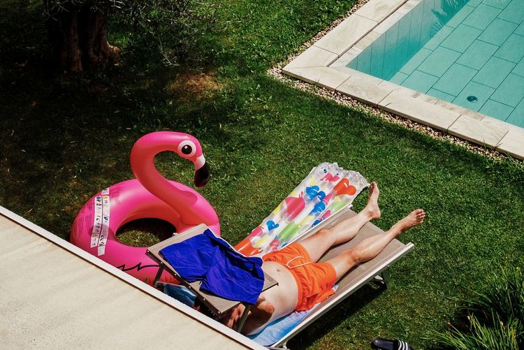 Man relaxing by swimming pool