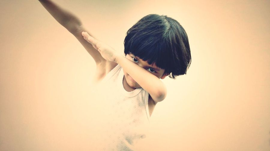 Portrait Of Boy Doing Dab Dance Against Beige Background