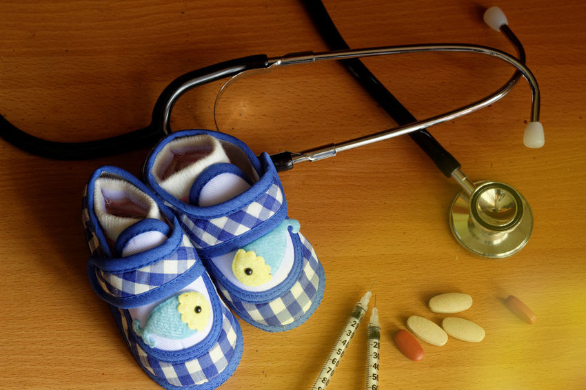 Stethoscope  Needle Syringe Close-up Pair Baby Shoes Baby Shoes Blue Pill Copyspace Wooden Medication Supplement Light Leak Insulin Gestational Pregnancy Diabetes Family Planning Contraception Side Lighting Medical Concept Conceptual