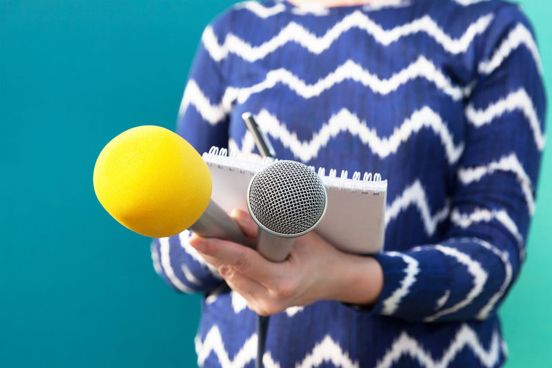 Public relations - PR. Press interview. Reporter. Microphone. Journalist PR Press Writing Writing Notes Broadcast Broadcasting Journalism Communication Female Human Hand Information Media Event Media Interview Microphone News News Conference Press Conference Public Relations Report