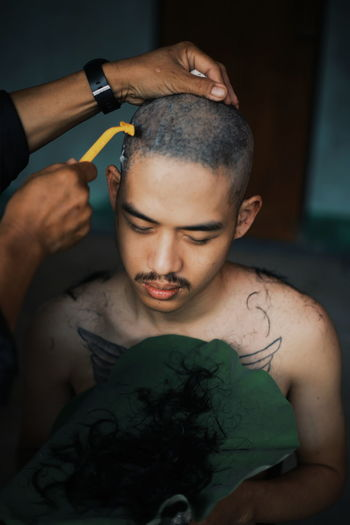 Cropped hands of person shaving shirtless man head at home
