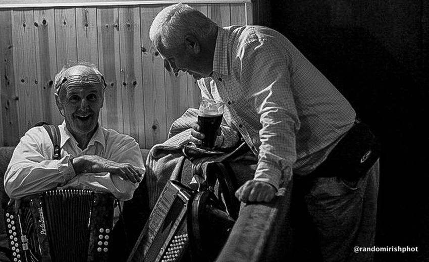 Two musicians share a joke during a break in performance in a pub in Mohill, Co Leitrim. Eye For Photography Rural Ireland Eye4black&white  EE_Daily: Black And White