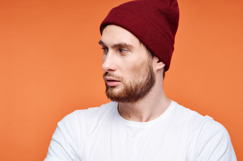 Portrait of young man looking away against orange background
