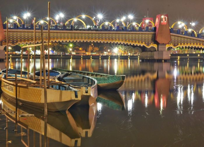 Boats moored in lake by illuminated bridge against sky at night