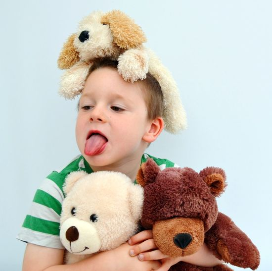 Cute boy with teddy bears sticking out tongue against white background