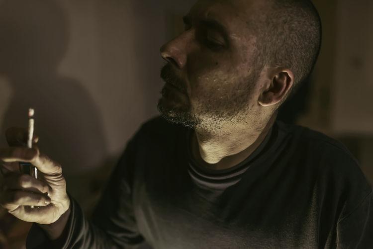 profile of a bearded man smoking a marijuana joint.close-up on a man smoking marijuana cigarette Addiction Addict Cannabis Cannabis - Narcotic Cannabiscommunity Drug Habit Joint Smoking  Marihuana Marihuana Legal Agriculture Substance Unhealthy Lifestyle Abuse Closeupshot Hashish Smoker Problems Smoke Smoker Ganja