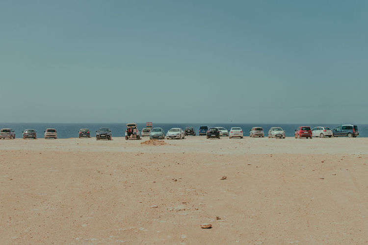 Cars Parked At Beach Against Sky
