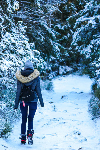 Full length rear view of woman in snow