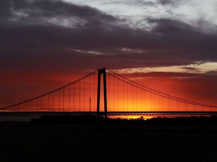Silhouette Of Suspension Bridge Against Cloudy Sky