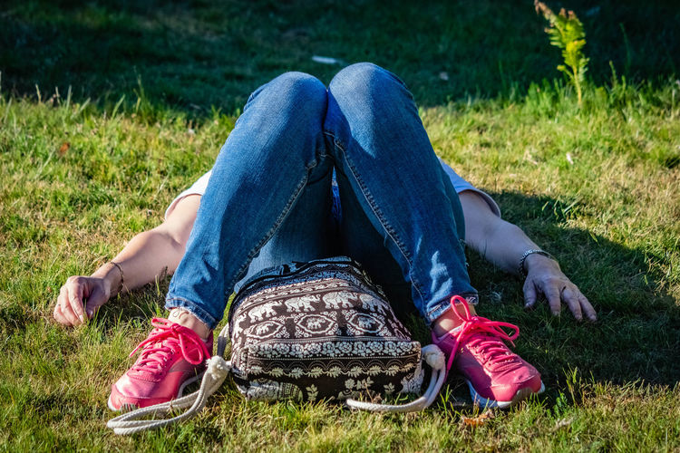 Low section of woman relaxing on grassy land