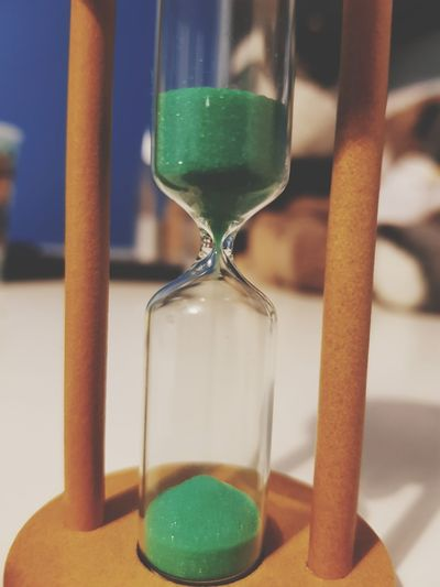 Close-up of hourglass with green sand