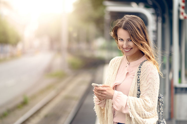 Attractive woman waiting on a platform Beauty In Nature Business Celebration City City Life Communication Commuting Happy Looking Looking At Camera Mobile Phone Morning One Person Platform Smart Phone Smiling Station Train Station Urban Waiting Wireless Technology Woman Ypung