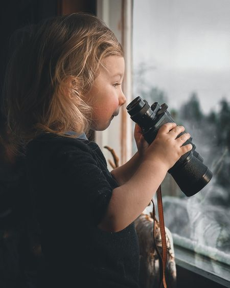 Side view of a boy with long hair holding binoculars