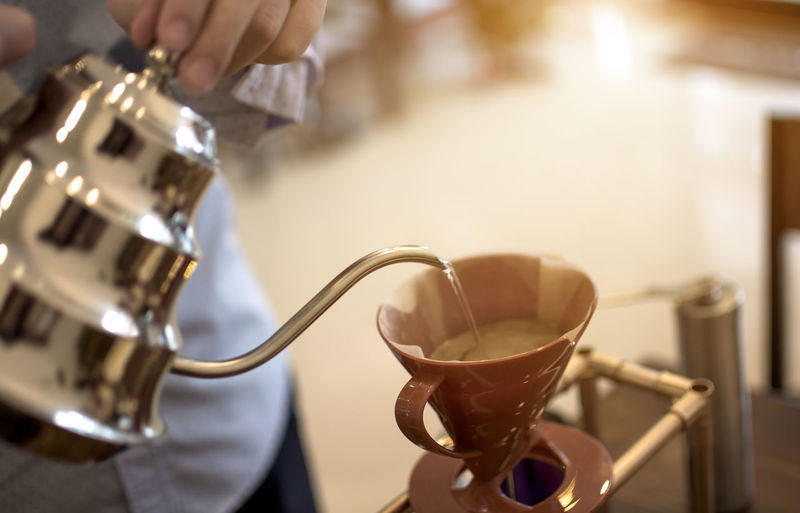 Close-up of hand pouring coffee cup