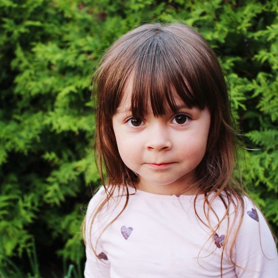 Close-Up Portrait Of Cute Girl Against Plants