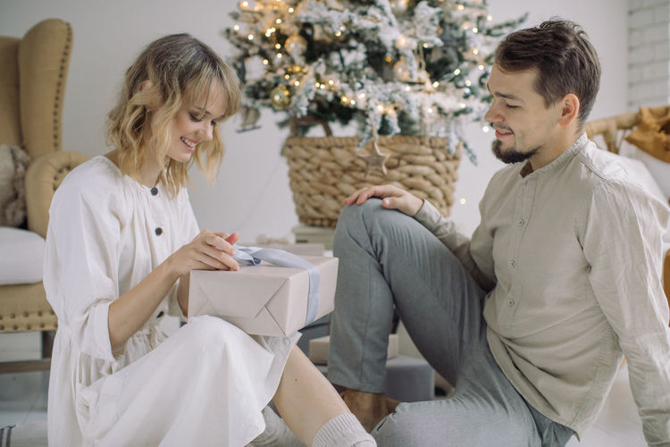 Man looking at girlfriend opening gift at home