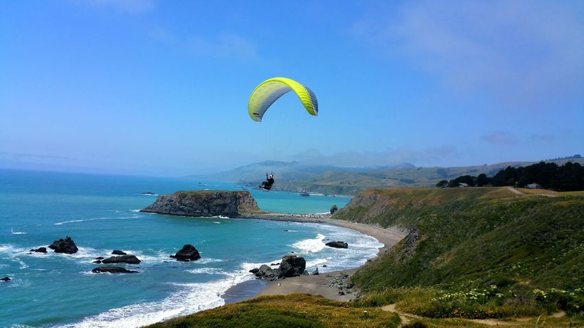 Paragliding Off of Ocean Cliffs ! Background Blue Sky Zen Timeless Copy Space Meditation Headland Waves Distance Aerial Chartreuse  Thrill Adventure Bucket List Dangerous Extreme Sports Sport Water Sea Beach Flying Paragliding Sport Blue Sky Parachute Gliding Exhilaration Extreme Sports Mid-air