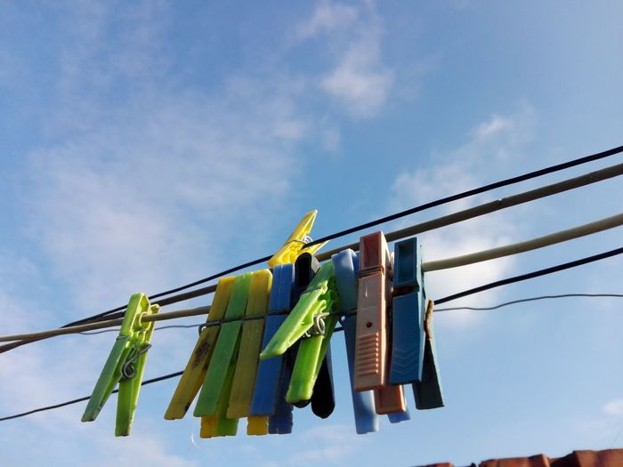 Low angle view of clothespins on clothesline against sky