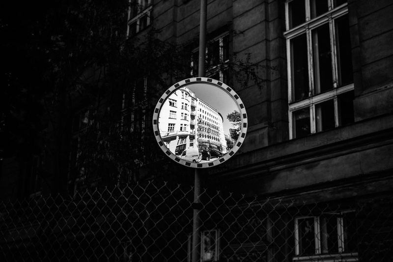 Low angle view of road mirror with reflection against building