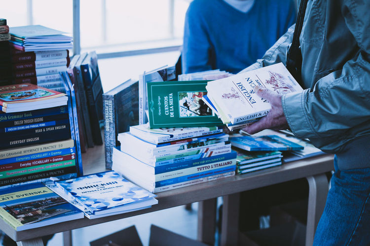 Midsection Of People With Books At Table