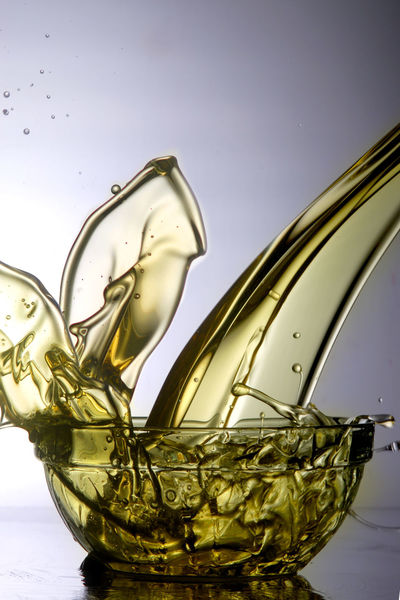 Liquid cooking oil splashes when poured into a glass bowl Container Cooking Flows Gold Golden Light Liquid Olive Overflow Bowl Drop Droplets Fluid Lubricant Lubrication Oil Petrol Poured Spilling Splash Splashes Splashing Stream Yellow