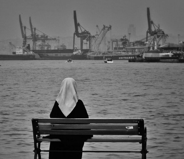 Rear view of woman sitting on bench by river against harbor