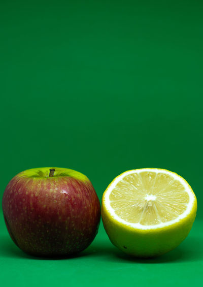 Close-up of apple on table against green background