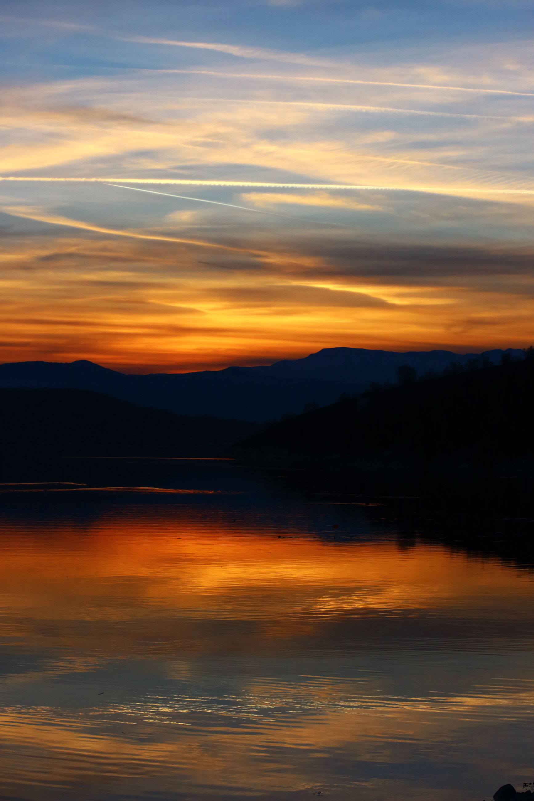 sunset, scenics, water, tranquil scene, tranquility, reflection, beauty in nature, orange color, sky, lake, idyllic, silhouette, mountain, nature, waterfront, cloud - sky, majestic, cloud, dramatic sky, calm