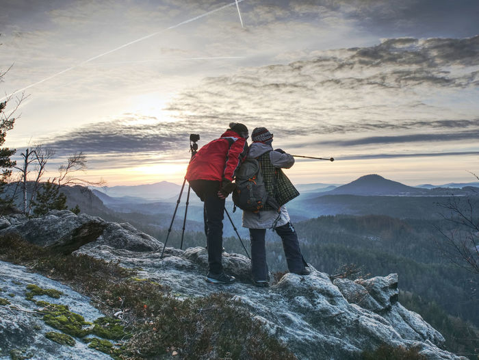 Couple enjoy photographying in wild nature. nature photographers stay on summit rock. listen to muse