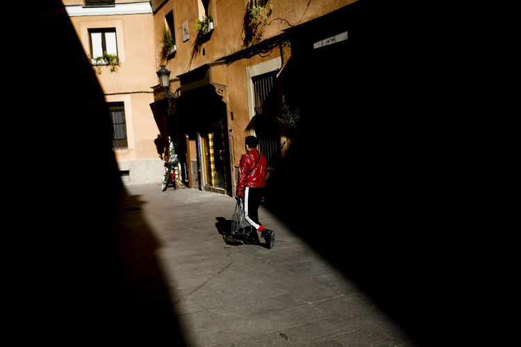 Building Exterior Architecture Built Structure City Real People Walking Building Shadow Street Men Lifestyles Sunlight Motion Full Length Day Incidental People People Rear View Group Of People Outdoors Alley