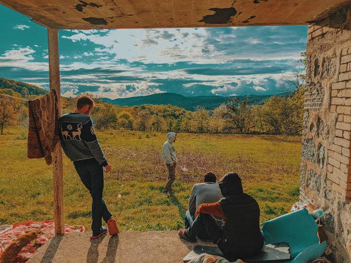 People sitting on landscape against mountain range
