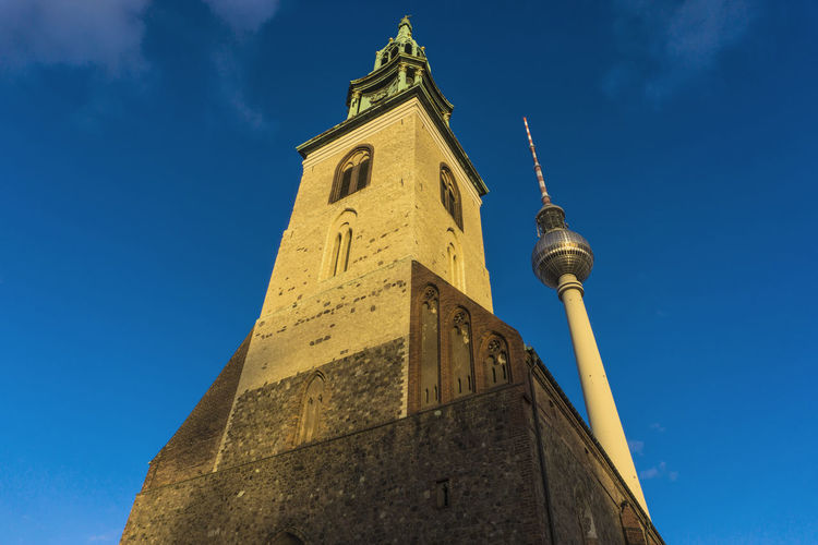 Low Angle View Of Marienkirche By Fernsehturm Against Blue Sky