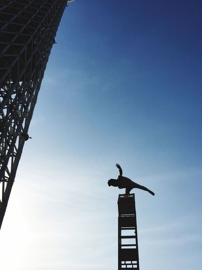 Low angle view of silhouette man on pole by tokyo sky tree against sky