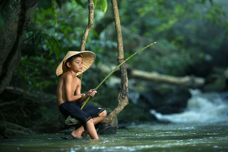 Full length of shirtless boy holding water in river